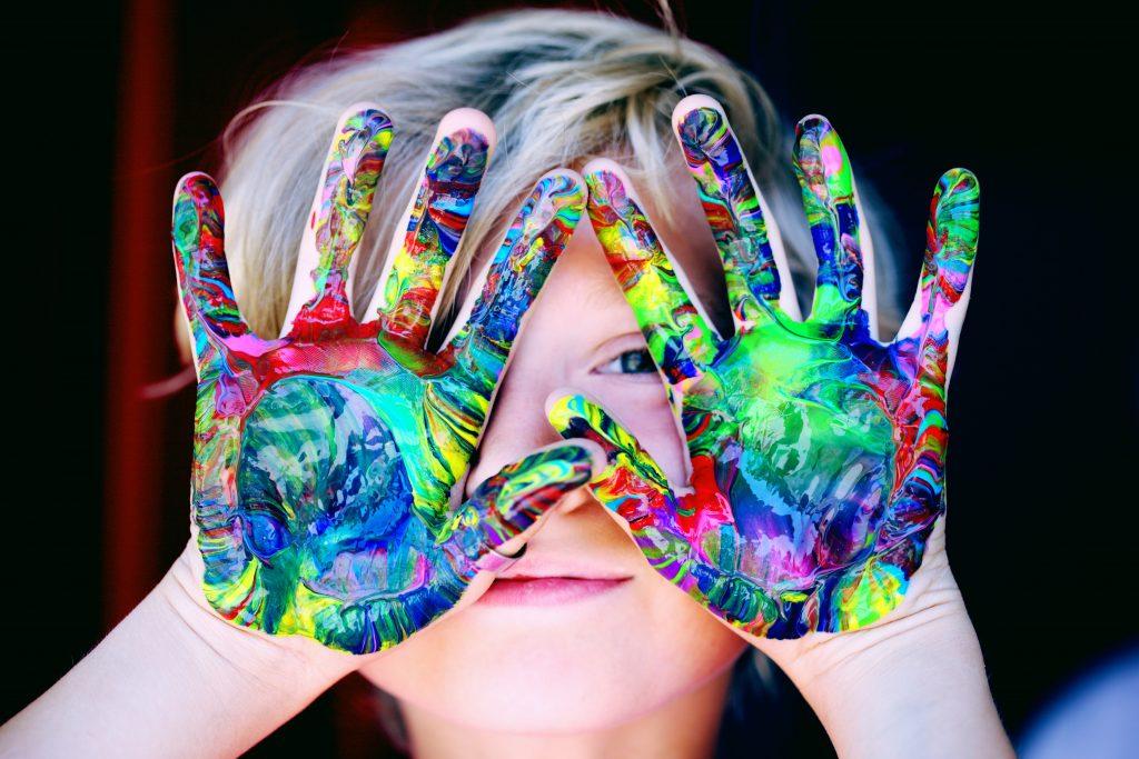 bambino biondo con mani dipinte di colori