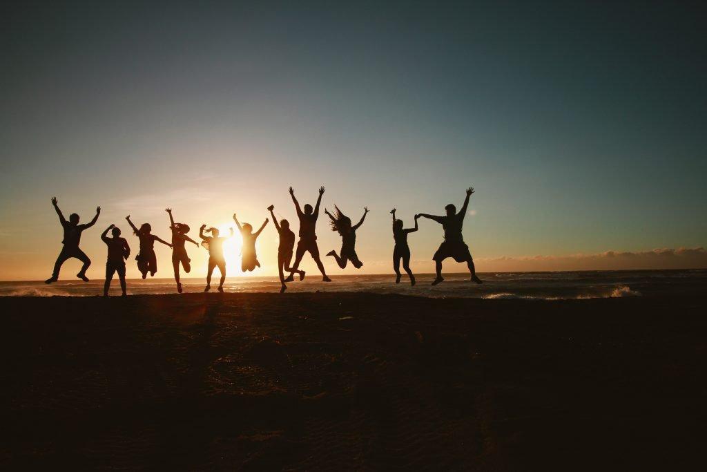 ragazzi che saltano in riva al mare al tramonto