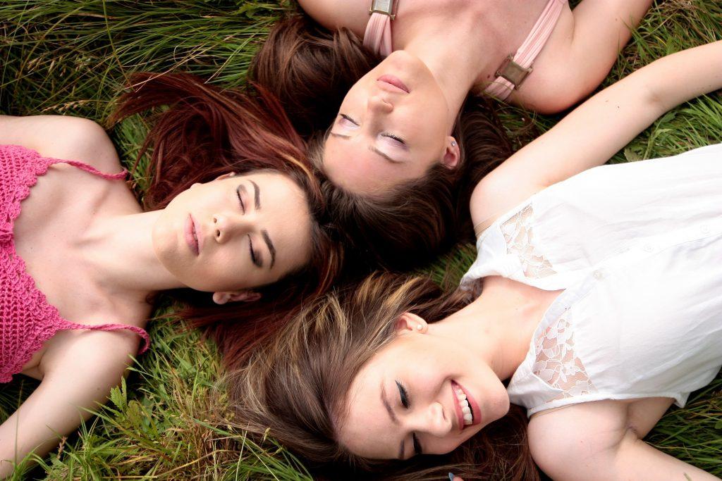 tre amiche sdraiate sull'erba
