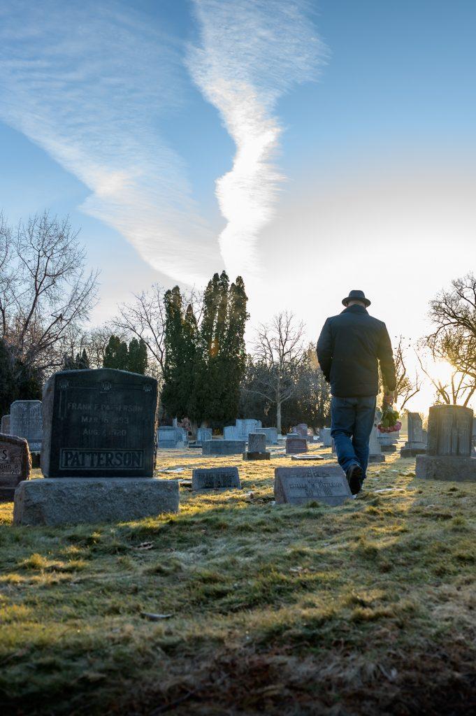 uomo con mazzo di fiori dentro un cimitero